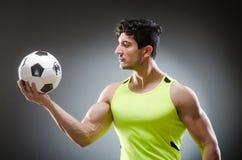 Το μυϊκό άτομο με τη σφαίρα ποδοσφαίρου Στοκ Φωτογραφία