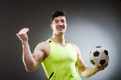 Το μυϊκό άτομο με τη σφαίρα ποδοσφαίρου Στοκ φωτογραφία με δικαίωμα ελεύθερης χρήσης