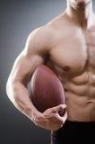Το μυϊκό άτομο με το αμερικανικό ποδόσφαιρο στοκ φωτογραφίες