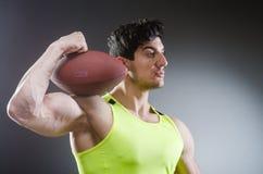 Το μυϊκό άτομο με το αμερικανικό ποδόσφαιρο στοκ εικόνα