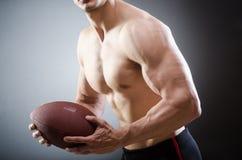 Το μυϊκό άτομο με το αμερικανικό ποδόσφαιρο στοκ φωτογραφία με δικαίωμα ελεύθερης χρήσης