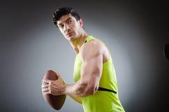 Το μυϊκό άτομο με το αμερικανικό ποδόσφαιρο στοκ εικόνα με δικαίωμα ελεύθερης χρήσης