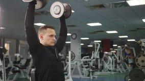 Το μυϊκό άτομο στη γυμναστική ανυψώνει τα βάρη καθμένος σε έναν πάγκο απόθεμα βίντεο