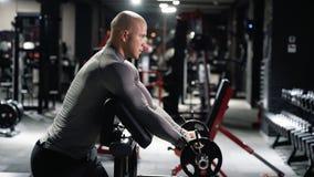 Το μυϊκό άτομο sportswear στην κατάρτιση στη γυμναστική με ένα barbell που κάνει τους δικέφαλους μυς ασκεί φιλμ μικρού μήκους