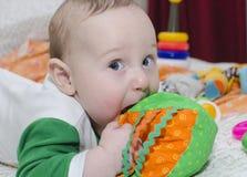 Το μωρό δαγκώνει το παιχνίδι, κινηματογράφηση σε πρώτο πλάνο στοκ εικόνα
