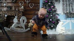 Το μωρό λαμβάνει τα πρώτα μέτρα του στη μητέρα της στο στούντιο με το ντεκόρ Χριστουγέννων απόθεμα βίντεο