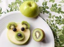 Το μωρό αντέχει το πρόσωπο φιαγμένο από φρούτα, επιδόρπιο διασκέδασης για τα παιδιά Στοκ εικόνες με δικαίωμα ελεύθερης χρήσης