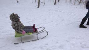 Το μωρό απολαμβάνει το χειμώνα γύρου ελκήθρων Υπαίθρια ενεργά παιδιά διασκέδασης 4K απόθεμα βίντεο
