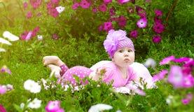 Το μωρό βρίσκεται στη χλόη στα λουλούδια Στοκ Εικόνες