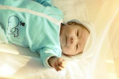 Το μωρό βρίσκεται στο κρεβάτι Ιδέες προϊόντων για τα παιδιά, παιχνίδια μωρών, οικογένεια Στοκ Εικόνες