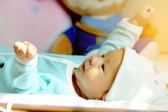 Το μωρό βρίσκεται στο κρεβάτι Ιδέες προϊόντων για τα παιδιά, παιχνίδια μωρών, οικογένεια Στοκ φωτογραφία με δικαίωμα ελεύθερης χρήσης