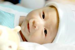 Το μωρό βρίσκεται στο κρεβάτι Ιδέες προϊόντων για τα παιδιά, παιχνίδια μωρών, οικογένεια Στοκ Φωτογραφία