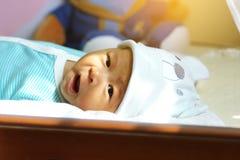 Το μωρό βρίσκεται στο κρεβάτι Ιδέες προϊόντων για τα παιδιά, παιχνίδια μωρών, οικογένεια, αύξηση Στοκ Φωτογραφία