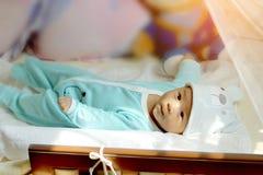 Το μωρό βρίσκεται στο κρεβάτι Ιδέες προϊόντων για τα παιδιά, παιχνίδια μωρών, οικογένεια, αύξηση Στοκ Φωτογραφίες
