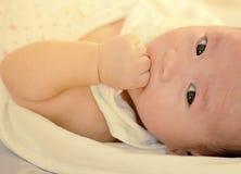Το μωρό βρίσκεται στο κρεβάτι Ιδέες προϊόντων για τα παιδιά, παιχνίδια μωρών, οικογένεια, αύξηση Στοκ φωτογραφία με δικαίωμα ελεύθερης χρήσης
