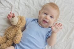 Το μωρό βρίσκεται στο πάτωμα με μια teddy αρκούδα Ένα παιδί που κυματίζει δικών του στοκ φωτογραφία με δικαίωμα ελεύθερης χρήσης