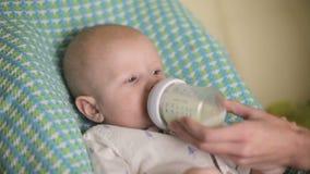Το μωρό κάθεται στην καρέκλα παιδιών ` s Το Mom ταΐζει το φωνάζοντας παιδί από το μωρό-μπουκάλι Κινηματογράφηση σε πρώτο πλάνο φιλμ μικρού μήκους