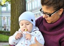 Το μωρό κάθεται στην περιτύλιξη μητέρων και τρώει τη σφαίρα καλαμποκιού Στοκ Εικόνα