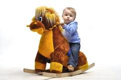 Το μωρό κάθεται στο ξύλινο άλογο παιχνιδιών στο στούντιο Στοκ Φωτογραφίες