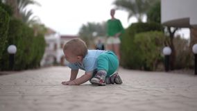 Το μωρό κάθεται στο πεζοδρόμιο και κοιτάζει κάτω από το θάμνο - αστεία δράση απόθεμα βίντεο