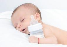 Το μωρό κατσάρωσε επάνω να κοιμηθεί σε ένα κάλυμμα με τη σίτιση του μπουκαλιού Στοκ Εικόνες