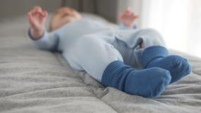 Το μωρό κινεί τα πόδια της που ντύνονται στις μπλε κάλτσες E φιλμ μικρού μήκους