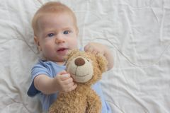 Το μωρό με τις συντηρήσεις μια teddy αρκούδα στοκ εικόνες με δικαίωμα ελεύθερης χρήσης