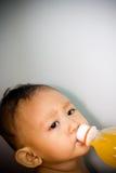 το μωρό πίνει το πορτοκάλι χυμού Στοκ εικόνες με δικαίωμα ελεύθερης χρήσης