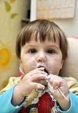 Το μωρό προσπαθεί να φάει το γιαούρτι ανεξάρτητα Στοκ Εικόνες