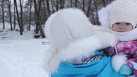 Το μωρό σε ετοιμότητα της μητέρας μου περπατά το χειμώνα στο άσπρο χιόνι την παγωμένη ημέρα Μητέρα με το παιδί για τον περίπατο σ απόθεμα βίντεο