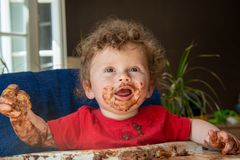 Το μωρό τρώει ένα κέικ σοκολάτας Στοκ εικόνα με δικαίωμα ελεύθερης χρήσης