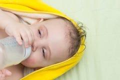 Το μωρό τρώει από ένα μπουκάλι Στοκ Εικόνες