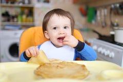 Το μωρό τρώει τις τηγανίτες Στοκ Φωτογραφίες