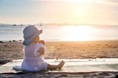 Το μωρό teething Όλα ροκανίζουν, μάσημα Συνεδρίαση κοριτσιών νηπίων στην τροπική παραλία άμμου και έρευνα του ηλιοβασιλέματος στοκ εικόνα με δικαίωμα ελεύθερης χρήσης