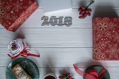 Το νέοι έτος και ο χειμώνας θέτουν στο άσπρο ξύλινο υπόβαθρο με τις κόκκινες και πράσινες και άσπρες λεπτομέρειες, ριγωτούς χρυσό Στοκ Εικόνες