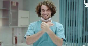 Το νέος άτομο ή ο γιατρός οδοντιάτρων στην κινηματογράφηση σε πρώτο πλάνο νοσοκομείων που φαίνεται ευθεία στη κάμερα και έβγαλε τ φιλμ μικρού μήκους