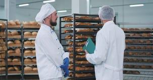 Το νέο άτομο αρτοποιών και ο κύριος μηχανικός έχουν μια συνομιλία σε ένα τμήμα αρτοποιείων με τα μέρη των ραφιών με το φρέσκο ψημ απόθεμα βίντεο