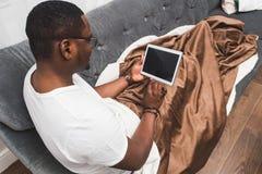 Το νέο άτομο αφροαμερικάνων, που καλύπτεται με ένα κάλυμμα, χρησιμοποιεί την ταμπλέτα στοκ εικόνες