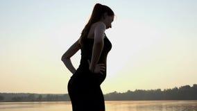 Το νέο έγκυο κορίτσι κάνει μια στάση οκλαδόν διάσπασης στο ηλιοβασίλεμα σε μια ακτή λιμνών 4k απόθεμα βίντεο