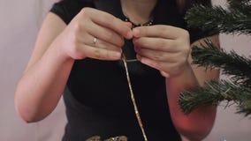 Το νέο έτος, γυναίκα Χριστουγέννων διακοσμεί ένα χριστουγεννιάτικο δέντρο απόθεμα βίντεο