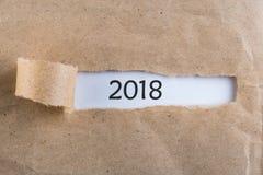 Το νέο έτος 2018 είναι ερχόμενη έννοια Μήνυμα καλής χρονιάς 2018 που εμφανίζεται πίσω από το σχισμένο καφετί έγγραφο στοκ φωτογραφία με δικαίωμα ελεύθερης χρήσης