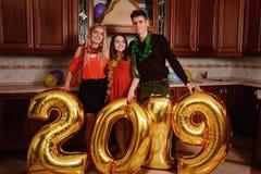 Το νέο έτος του 2019 έρχεται Η ομάδα εύθυμων νέων που φέρνουν τους χρυσούς χρωματισμένους αριθμούς και έχει τη διασκέδαση στο κόμ στοκ εικόνα με δικαίωμα ελεύθερης χρήσης