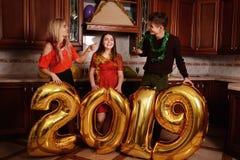 Το νέο έτος του 2019 έρχεται Η ομάδα εύθυμων νέων που φέρνουν τους χρυσούς χρωματισμένους αριθμούς και έχει τη διασκέδαση στο κόμ στοκ φωτογραφίες