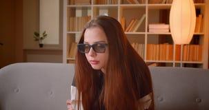 Το νέο έφηβη στα τρισδιάστατα γυαλιά προσέχει την ταινία στη συνεδρίαση TV στον καναπέ στο υπόβαθρο ραφιών στο σπίτι απόθεμα βίντεο