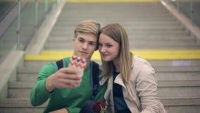 Το νέο αγαπώντας ζεύγος παίρνει selfie τη συνεδρίαση στα βήματα του κολλεγίου φιλμ μικρού μήκους