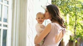 Το νέο αγκάλιασμα mom και δίνει τα φιλιά στη γλυκιά μούμια παιδιών στο κατώφλι φιλμ μικρού μήκους