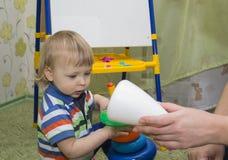 Το νέο αγόρι βάζει μια πυραμίδα στον παιδικό σταθμό, στο υπόβαθρο των παιχνιδιών παιδιών ` s Στοκ Εικόνες