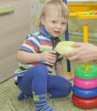 Το νέο αγόρι βάζει μια πυραμίδα στον παιδικό σταθμό, στο υπόβαθρο των παιχνιδιών παιδιών ` s Στοκ φωτογραφία με δικαίωμα ελεύθερης χρήσης