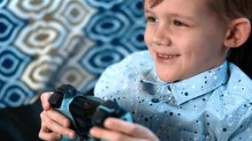 Το νέο αγόρι παίζει το τηλεοπτικό παιχνίδι με το πηδάλιο και την παρουσίαση μερών των συγκινήσεων απόθεμα βίντεο