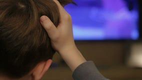 Το νέο αγόρι που προσέχει τη TV βλέπει στο σπίτι από την πλάτη απόθεμα βίντεο